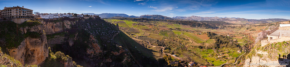 From the viewpoint Mirador de Ronda close to bullfighting ring you can enjoy a view of olive plantations and fields that spread out down in the valley in front of the city and are surrounded by the mountain range far on the horizon. Andalusia, Andalucia, Spain.