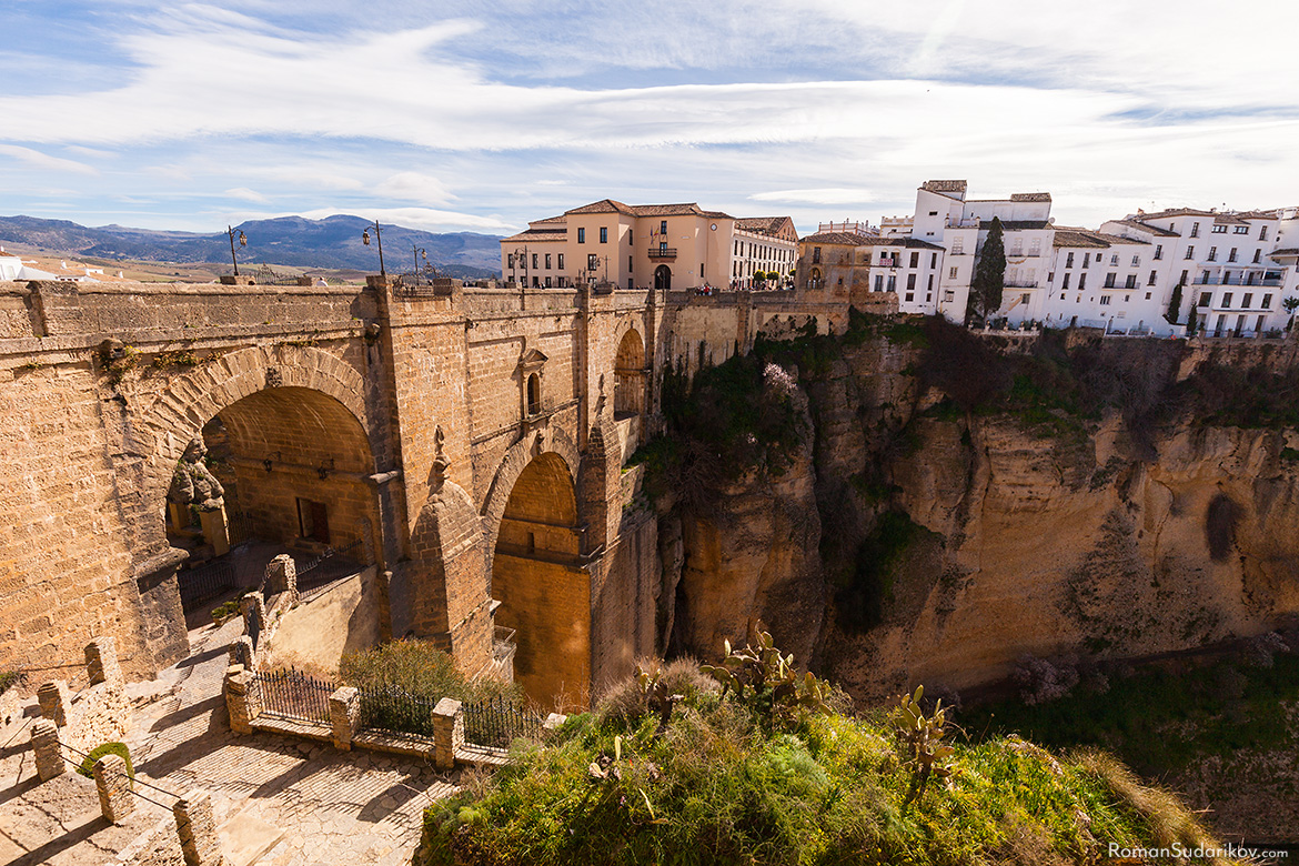 "Three arch bridge Puente Nuevo, which means in English ""New Bridge"", over the El Tajo gorge, is connecting the old and the new parts of the town Ronda. This view is from the west side of the bridge. Andalusia, Andalucia, Spain."