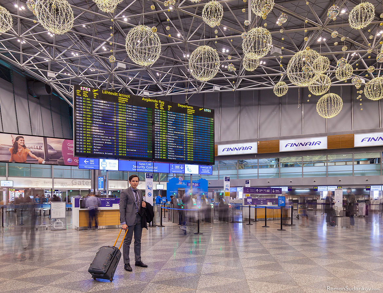 Роман Судариков в аэропорту Хельсинки-Вантаа ждёт вылет самолёта в Испанию. Он в костюме и с чемоданом. Хельсинки, Финляндия.