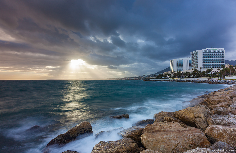 Лучи солнечного света пробиваются сквозь толстый слой хмурых туч и большие волны разбиваются о камни на берегу Торрекебрады, что находится в Бенальмадене. Коста дель Соль, Испания.