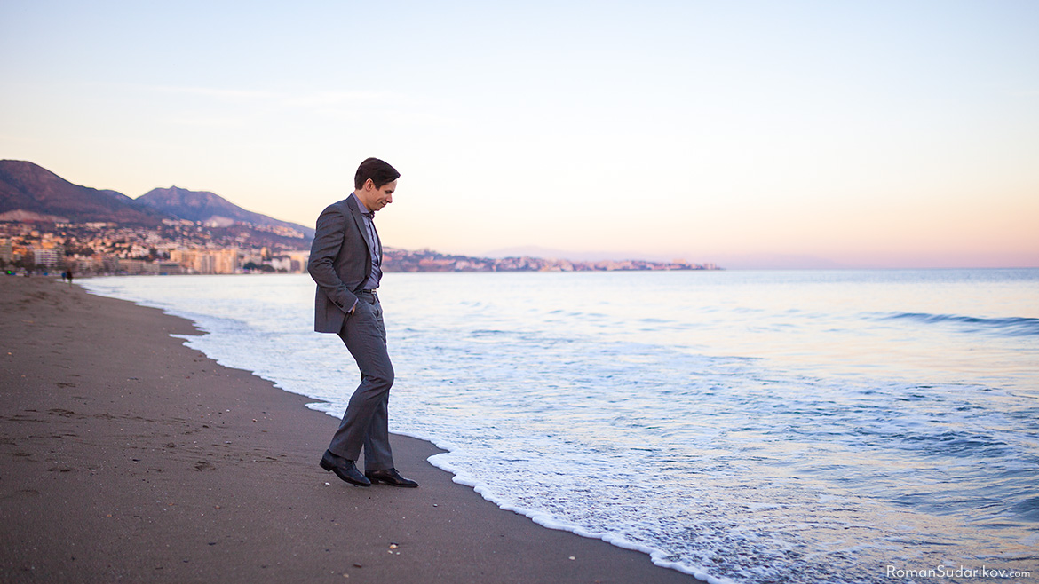 Roman Sudarikov is wearing a suit and dodging the waves at the beach of Fuengirola during sunset. Costa del Sol, Spain.