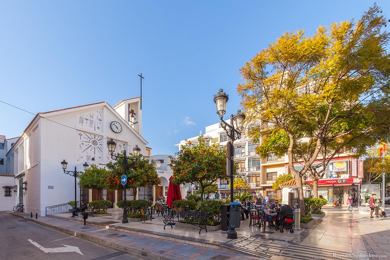 Люди обедают на открытом воздухе на маленькой площади перед церковью Parroquia Virgen del Carmen y Santa Fe в Фуэнхироле, в части города Лос Боличес. Коста дель Соль, Испания.