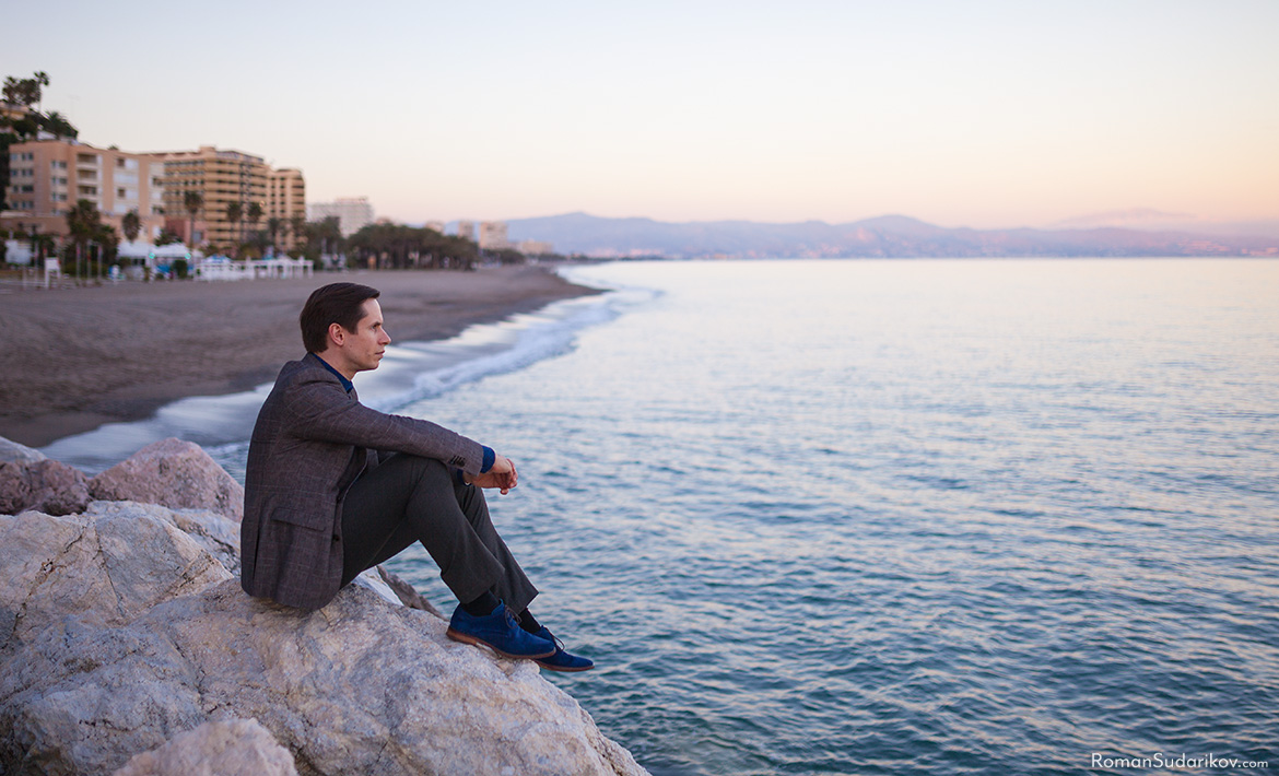 Roman Sudarikov is sitting on the rocks at the beach in Torremolinos during sunset. Costa del Sol, Spain.