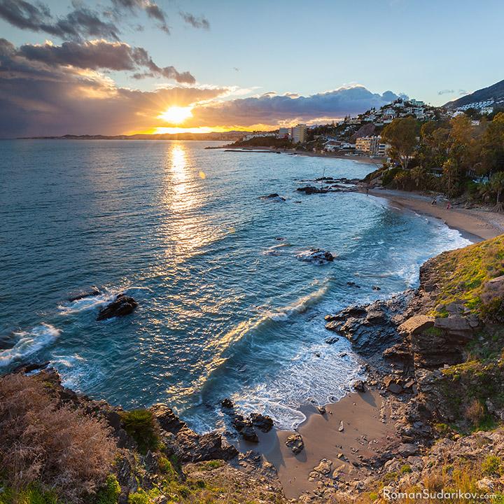 Аuringonlaskun aikaan Playa de la Viborilla nimisellä hiekkarannalla, joka sijaitsee Benalmadenassa, valkoharjuiset aallot vaahtoavat osuessa rantaan ja taivaalla on pilviä, joiden läpi paistavat viimeiset auringon säteet. Costa del Sol, Espanja.