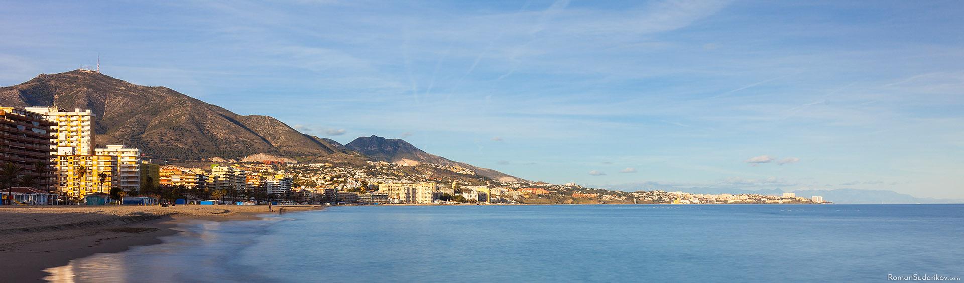 Мягкие волны на пляже Фуэнхиролы. На горизонте видны горы Бенальмадены, Серро дель Моро и за ней Каламорро. Коста дель Соль, Испания.