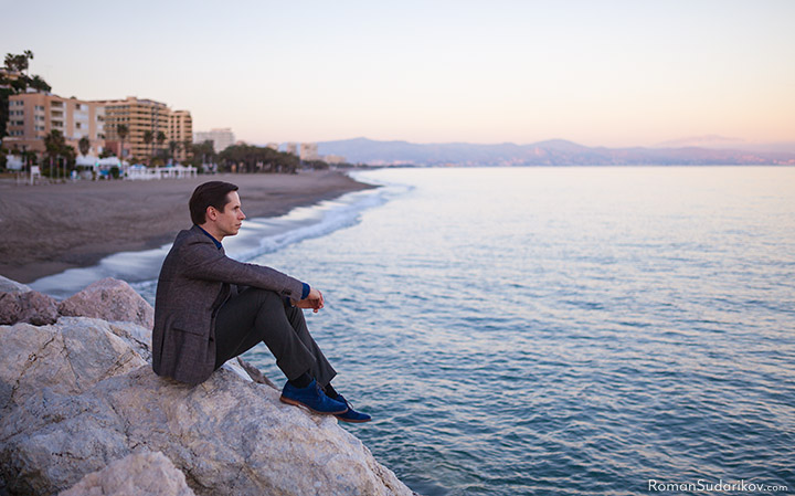 About myself, short biography, profile picture. Roman Sudarikov is sitting on the rocks at the beach in Torremolinos during sunset. Costa del Sol, Spain.