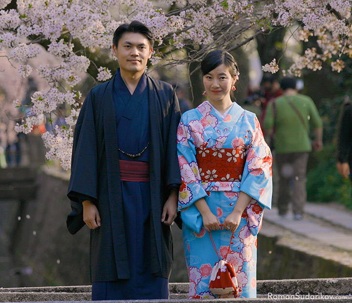 Young couple in beautiful kimono is standing close to each other under cherry blossom trees at Philosopher's Path in Kyoto.