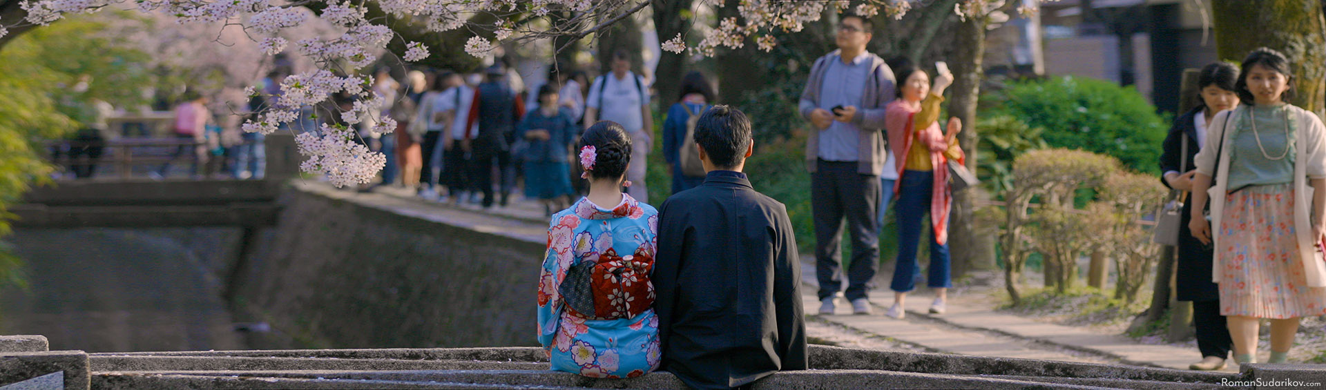Young couple in beautiful kimono is sitting close to each other under cherry blossom trees at Philosopher's Path in Kyoto.