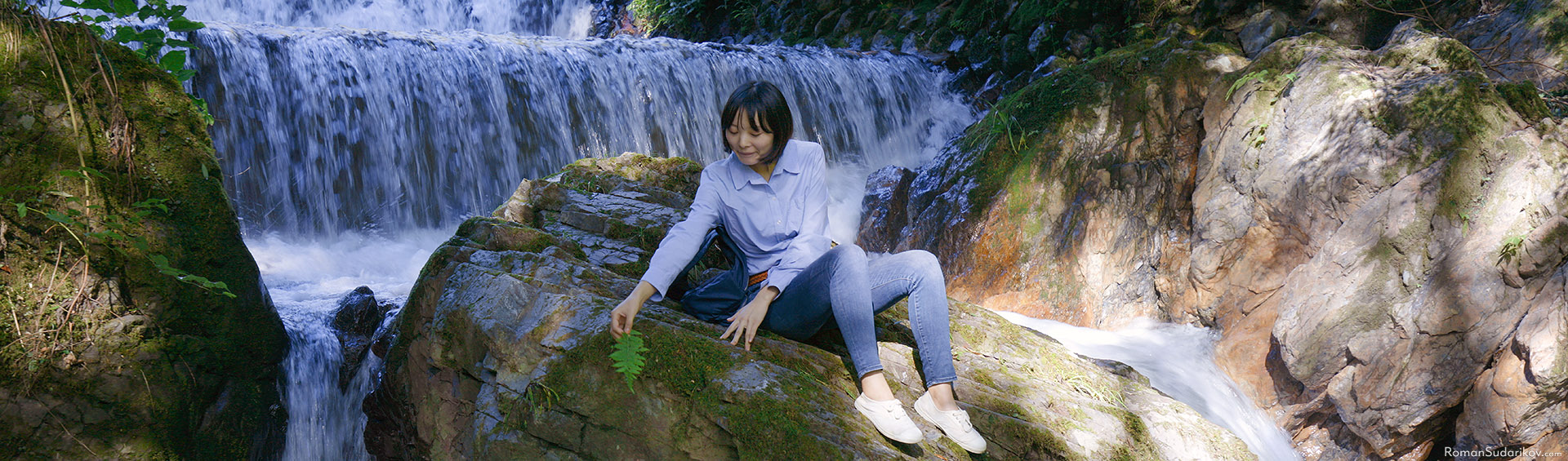 Young woman is sitting on the rock surrounded by water in Kibune, Kyoto.