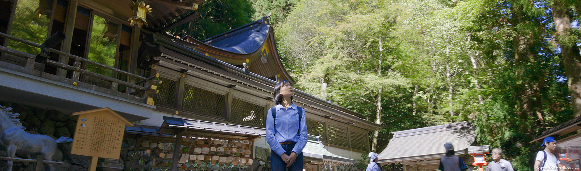 Young woman is standing in the middle of Kifune Jinja Shrine and looking around.