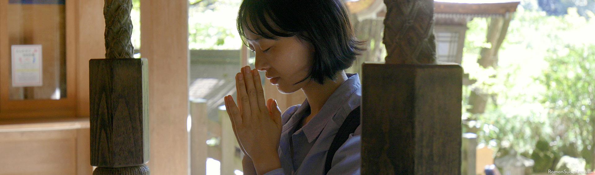 Young woman is praying at Kifune Jinja Shrine located in mountains near Kyoto.